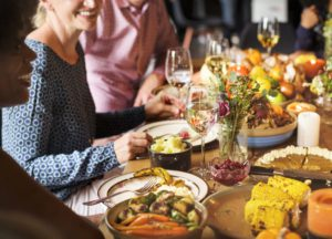 a group of people are gathered around a table set for Thanksgiving