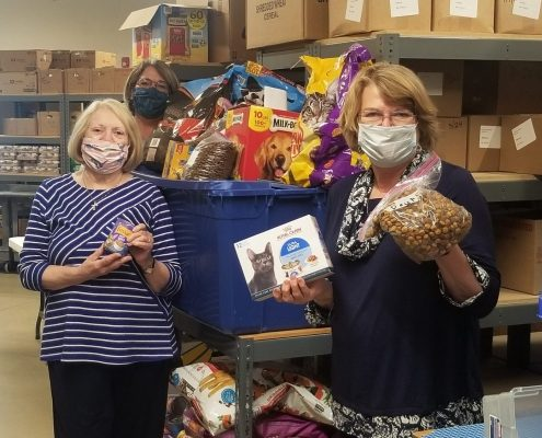 Women stand in a warehouse with a bin of prepackaged pet food