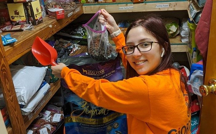 a smiling girl holds up a bag of pet food