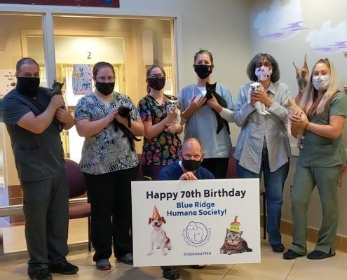 "a group of men and women in scrubs stand holding cats, while wearing face masks. A man kneels in front holding a sign with a cat and dog on it saying ""happy 70th birthday Blue Ridge Humane Society"""