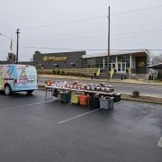"""image of a brightly decorated van with tables set up behind it with piles of bagged pet food. In the background in a modern looking one story building with """"boys and girls club of Henderson County"""" written on it."""