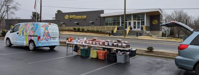 "image of a brightly decorated van with tables set up behind it with piles of bagged pet food. In the background in a modern looking one story building with ""boys and girls club of Henderson County"" written on it."
