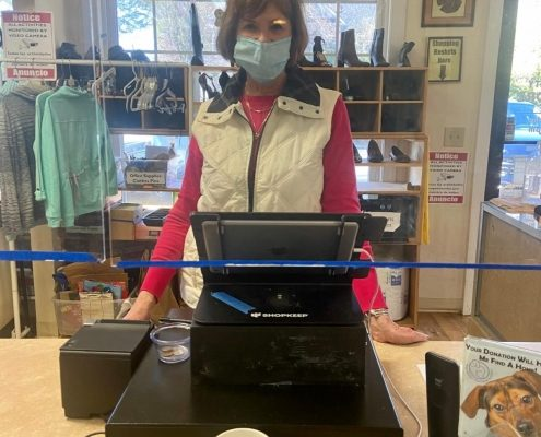 a woman wearing a mask stands behind a cash register
